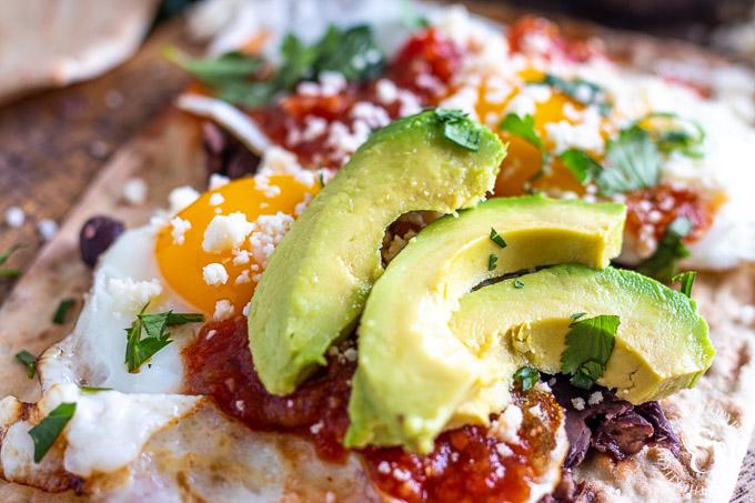 Flatbread Huevos Rancheros with sliced avocados